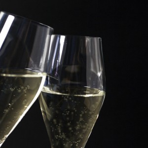 clicking champagne flutes against black background